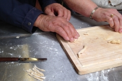 Men & Women shaping fresh pasta with ICA members/drop in centre